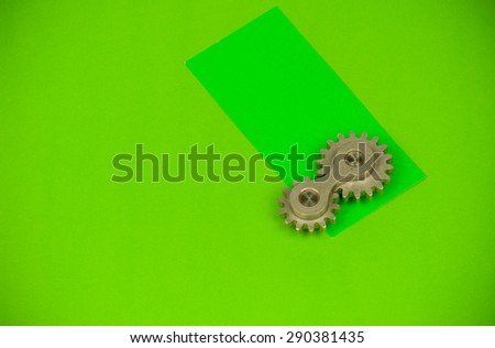 Arrangement of double cog wheel element with vibrant green card, showing funny playful approach to mechanical dynamics theoretical sciences and heavy machine industry terms and items - stock photo