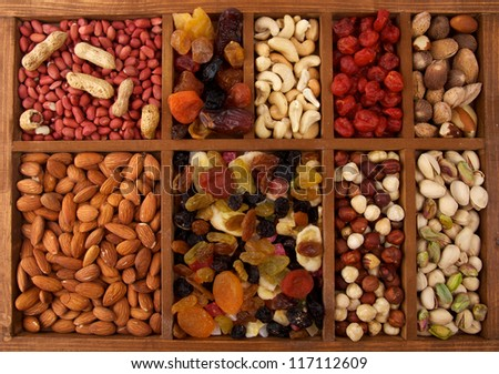 Arrangement of Dried Fruits and Nuts in Wooden Box closeup top view - stock photo