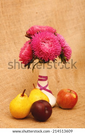 Arrangement of flowers and fruit. Aster flower in white vase on a table stand. Next to them are apple, pear, plum. Autumn still life of fresh fruit and flowers. Composition in yellow tones. Space text - stock photo