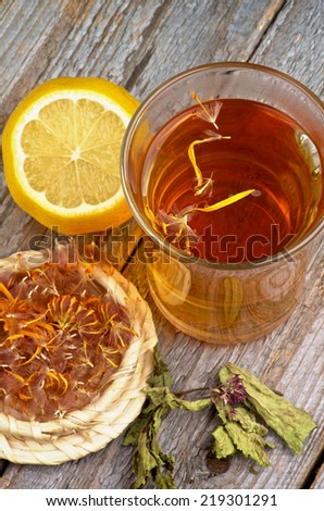 Arrangement of Healthful Herbal and Flower Tea in Glass Tea Cup, Dried Herbs and Lemon isolated on Rustic Wooden background. Top View
