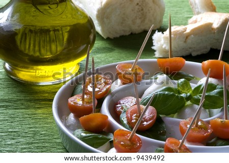Arrangement of mozzarella and tomatoes with basil and olive oil.