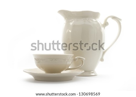 arrangement of porcelain teacups, saucer and jug isolated on white - stock photo