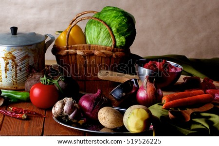Arrangement of Raw Ingredients with Vegetables, Meat, Spices and Kitchen Dish Ware closeup on Wooden background. Dutch Still Life Styled