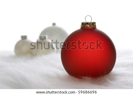 Arrangement of red and white Christmas baubles on white fur - stock photo