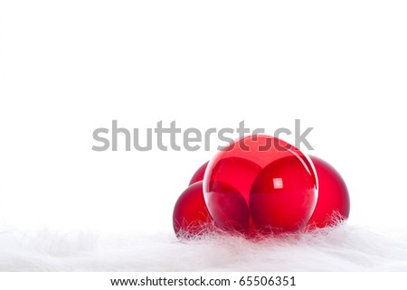 Arrangement of 4 red christmas baubles on white fur - stock photo