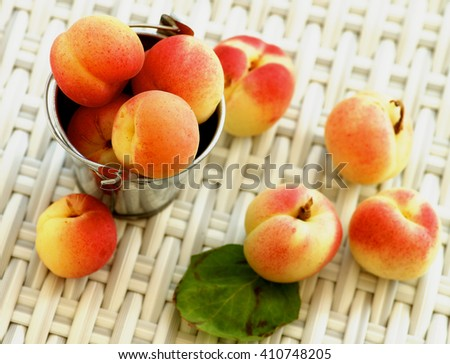 Arrangement of Ripe Fresh Apricots in Tin Bucket closeup on Wicker background. Focus on Top of Heap - stock photo