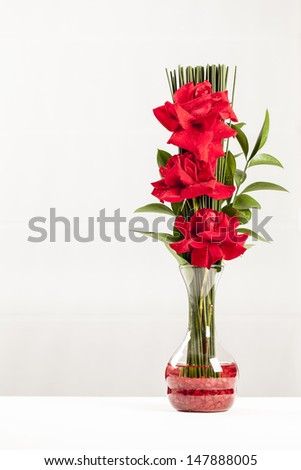 Arrangement of roses in a glass vase on a white background.