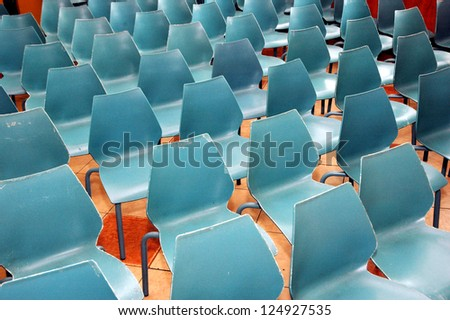 arrangement of rows of small blue chairs - stock photo