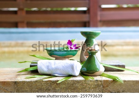 Arrangement of spa treatment products made out of massage oil in ceramic bottle, aromatherapy, scented oil and towel by poolside. - stock photo