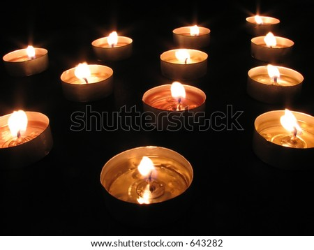 Arrangement of tea-lights with the centermost light in focus - stock photo