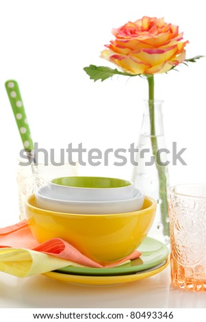 Arrangement of three colorful bowls, plates ,glasses and rose - stock photo