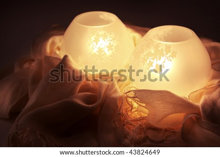 Arrangement of two lamps and a tasseled cloth. - stock photo