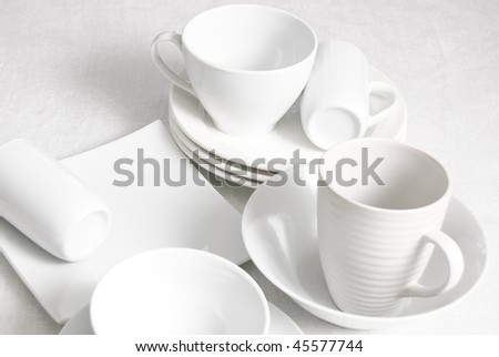 Arrangement of white ceramic dishes on a white tablecloth - stock photo