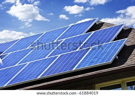 Array of alternative energy photovoltaic solar panels on roof - stock photo