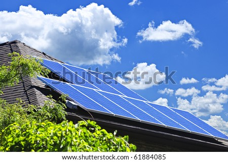 Array of alternative energy photovoltaic solar panels on roof of residential house - stock photo