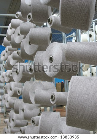 Array of cotton yarn spools (bobbins) in a textile factory - stock photo
