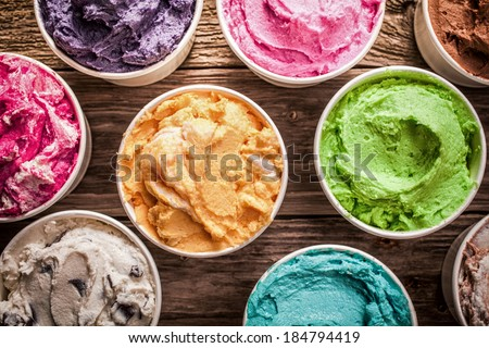 Array of different flavored colorful ice cream in plastic tubs displayed on an old wooden table at an ice cream parlor for delicious frozen snacks on a hot summer day - stock photo