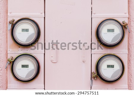 Array of four modern smart grid residential digital power supply watthour meters on grungy pink exterior wall - stock photo