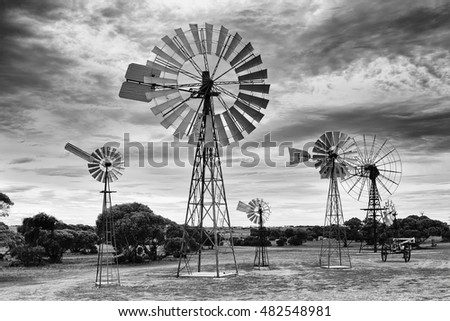 Array of historic traditional windmills in rural South Australia against cloudy sky on a hot summer day in black-white conversion.