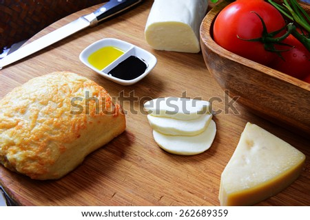 Array of parmesan & mozzarella cheeses with ciabatta, olive oil, balsamic vinegar, fresh tomato & ciabatta loaf on cutting board with knife in background - stock photo