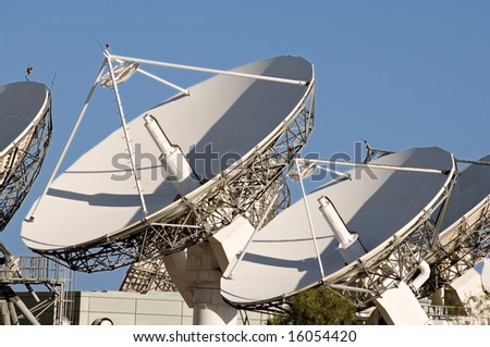 Array of satellite dishes against a blue sky - stock photo