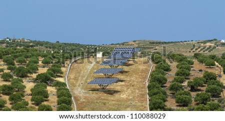 Array of solar panels in olive grove. Crete. Greece - stock photo