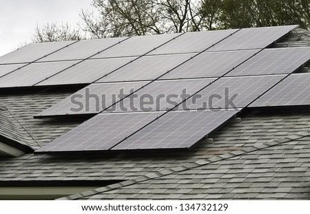 Array of solar panels on sloped roof of detached house on an overcast morning - stock photo