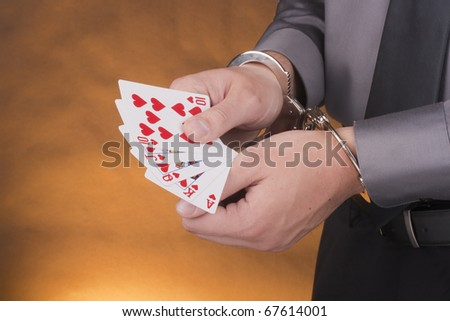 Arrest card sharper, her hands handcuffed in one hand a set of cards in one suit. - stock photo