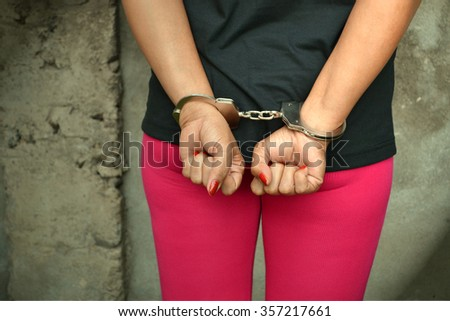Arrested female with hands cuffed standing against a wall - stock photo