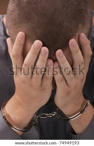 Arrested in handcuffs covered his face with his hands. - stock photo
