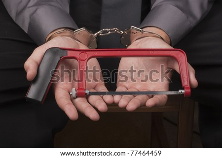 Arrested in handcuffs holding a hacksaw with a goal to remove the handcuffs. - stock photo