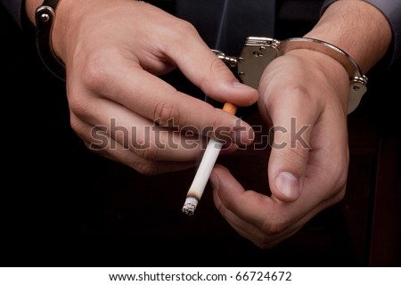 Arrested in handcuffs holding a smoking cigarette.
