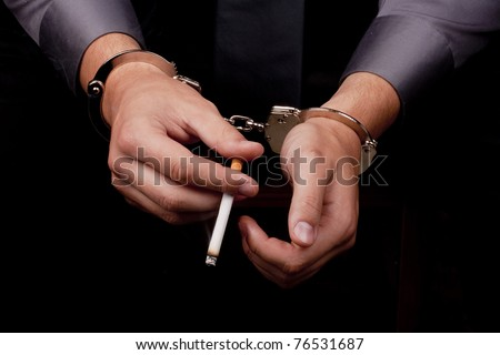 Arrested in handcuffs holding a smoking cigarette. - stock photo