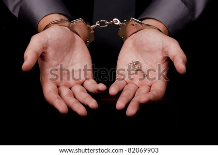 Arrested in handcuffs in his hands the key to the handcuffs. - stock photo
