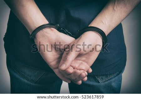 Arrested man in handcuffs with hands behind back close up