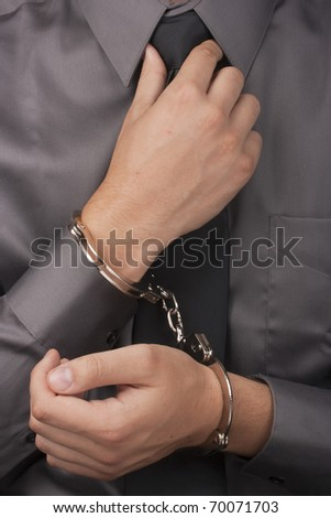 Arrested white man in handcuffs straightens his tie. - stock photo