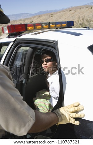 Arrested woman sitting in police car looking at traffic cop - stock photo