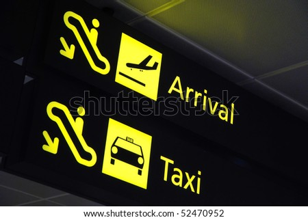 Arrival and taxi signages at the airport for concepts related to travel and transportation, aviation and airport, and vacation. - stock photo