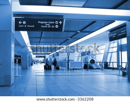 Arrival concourse at international airport with people walking toward luggage claim area - blue monochrome, focus on foreground sign - stock photo