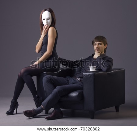 arrogant man and masked woman sitting in the chair over grey background - stock photo