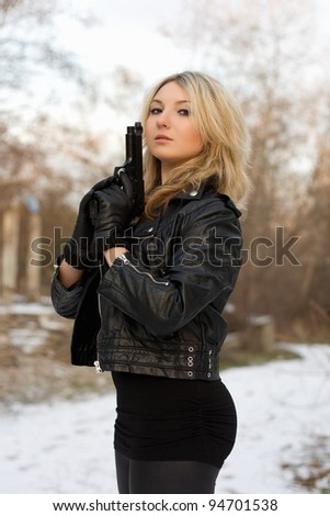 Arrogant pretty woman with a gun in winter forest - stock photo