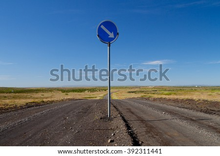 Arrow and direction in a desert road iceland - stock photo