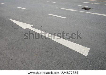 Arrow direction sign on asphalt road - stock photo