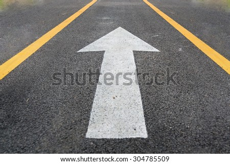 arrow in road,Bicycle road sign on asphalt. Leisure activitiesb,Bicycle road sign and bike rider. - stock photo