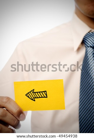 Arrow in yellow card showing direction holding by businessman. - stock photo