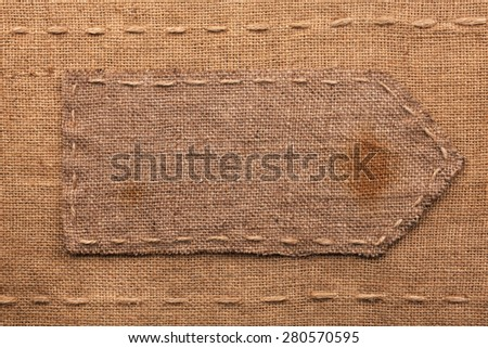 Arrow made of burlap  lies on a sacking  background,can be used as texture - stock photo