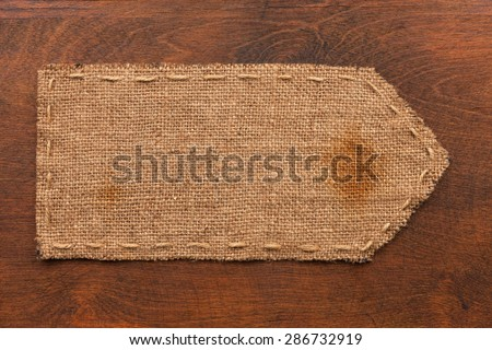 Arrow made of burlap lies on a wooden background, can be used as texture - stock photo