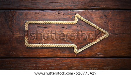 Arrow made of rope on a wooden background