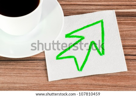 Arrow on a napkin and cup of coffee - stock photo