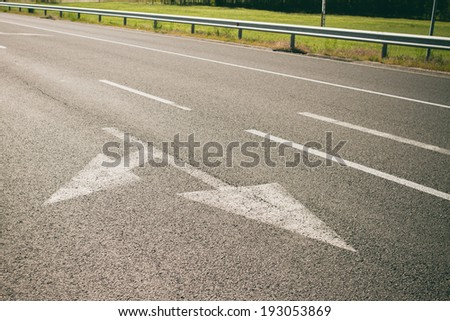arrow on asphalt showing traffic where to go